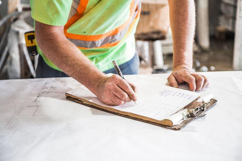 Artisan remplissant un document pour la vente d'un matériau de chantier